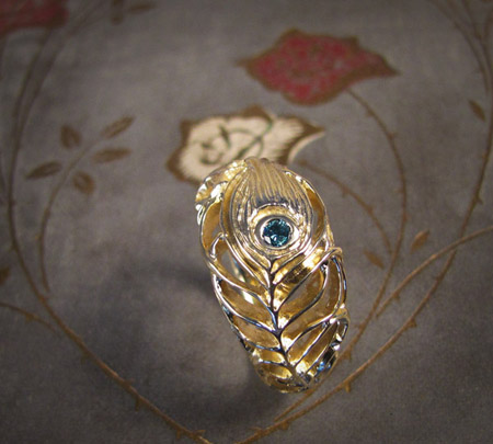 Carved peacock feather ring with blue diamond in 18K gold