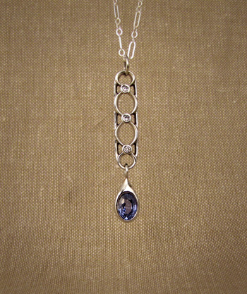 Art Deco-inspired palladium pendant with diamonds and a sapphire drop