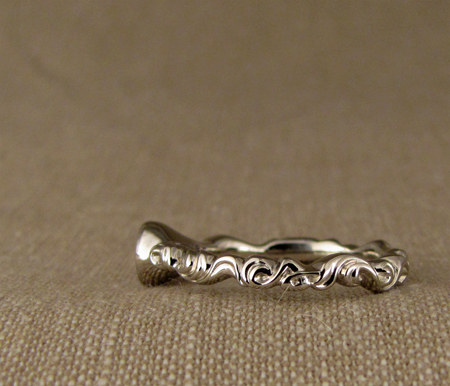Carved arabesque solitaire w/diamond; 18K white gold