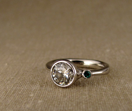 Diamond solitaire with emerald side stone; Palladium