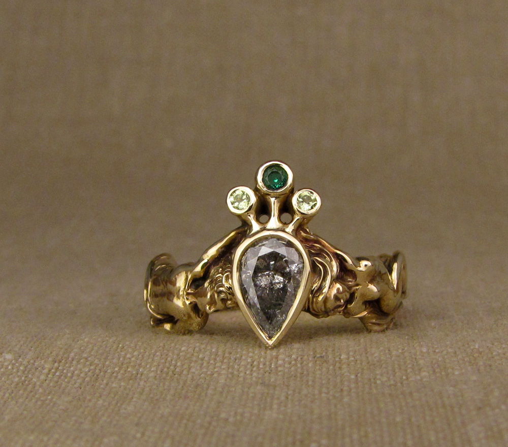 Crowned pear diamond solitaire with tiny gold carved man & woman down the sides of the ring