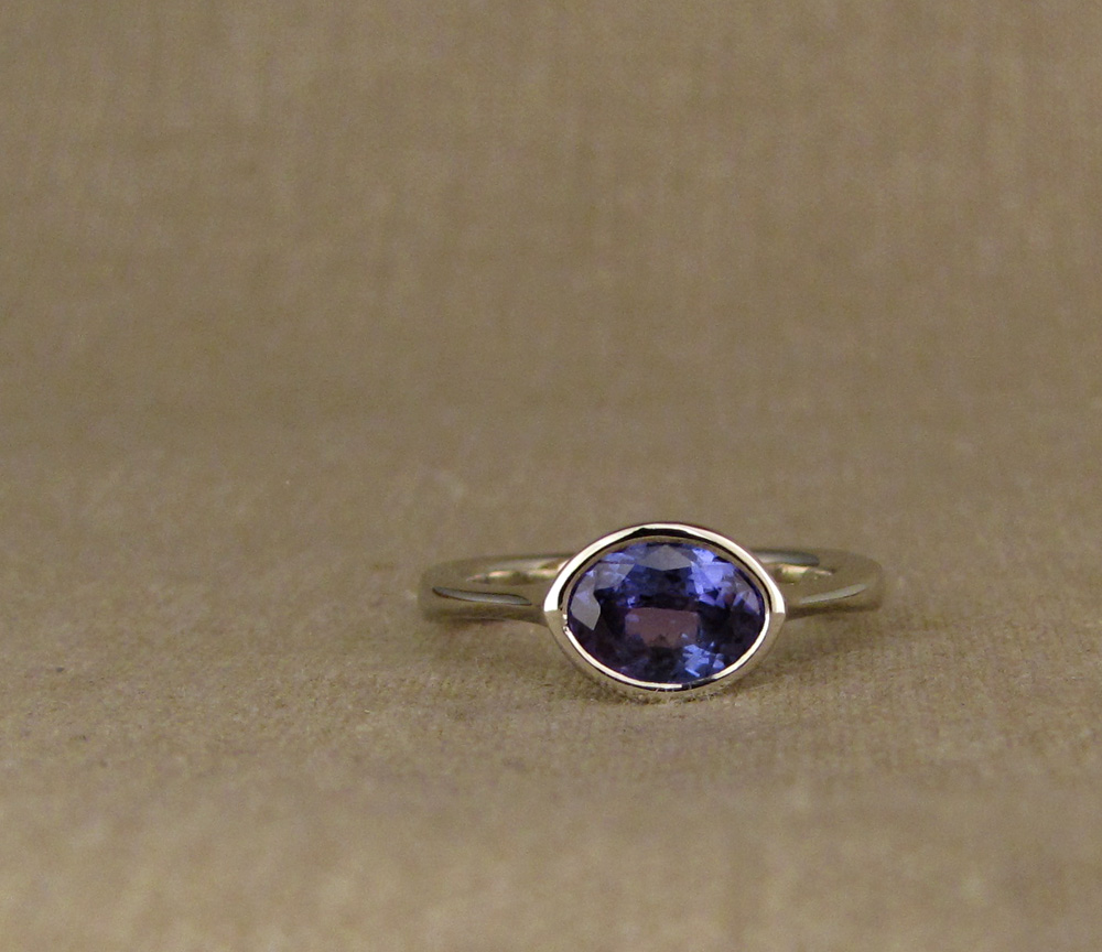Custom Low-Profile Bezel Solitaire with oval tanzanite, 14K white gold