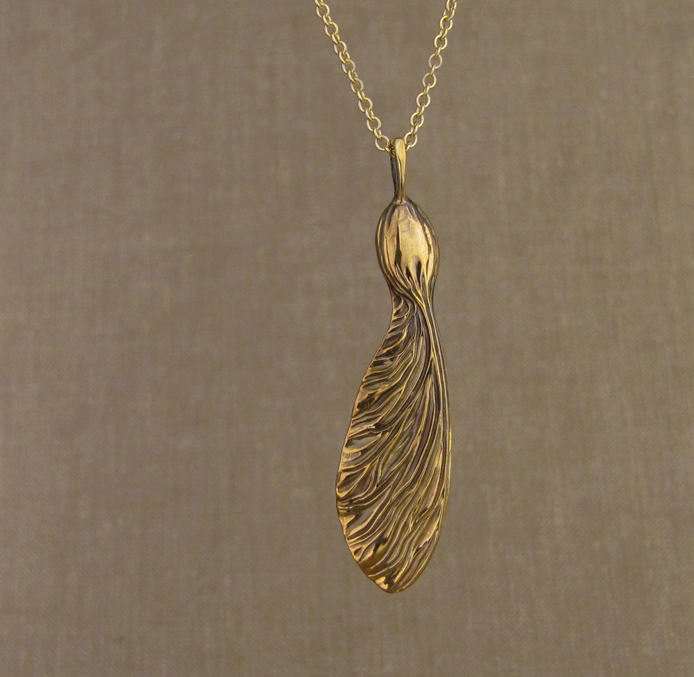 Hand-carved sycamore seed pendant in 18K yellow gold