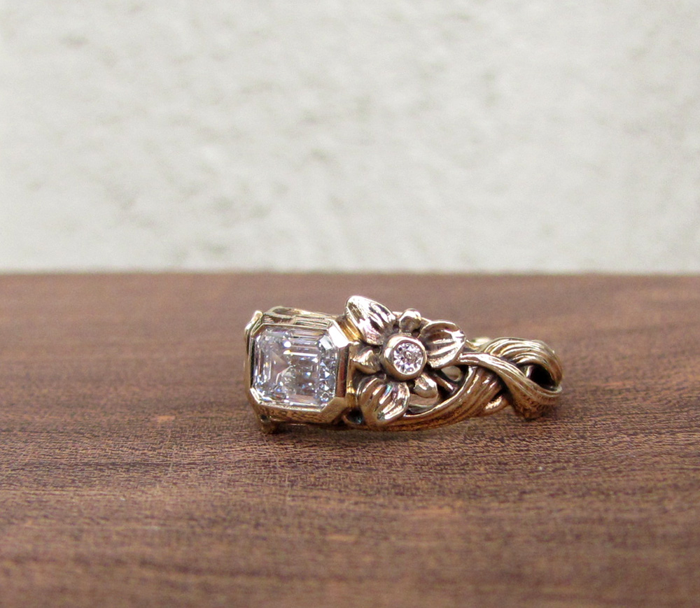 Custom-designed & hand-carved solitaire with 1ct emerald cut diamond. Lily flower, leaves, bulb motif.