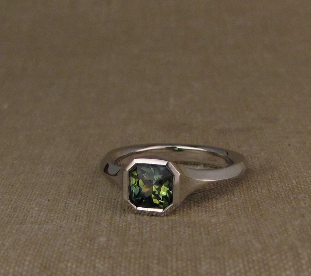 Custom hand-carved geometric solitaire for radiant-cut blue-green parti-sapphire. Platinum.