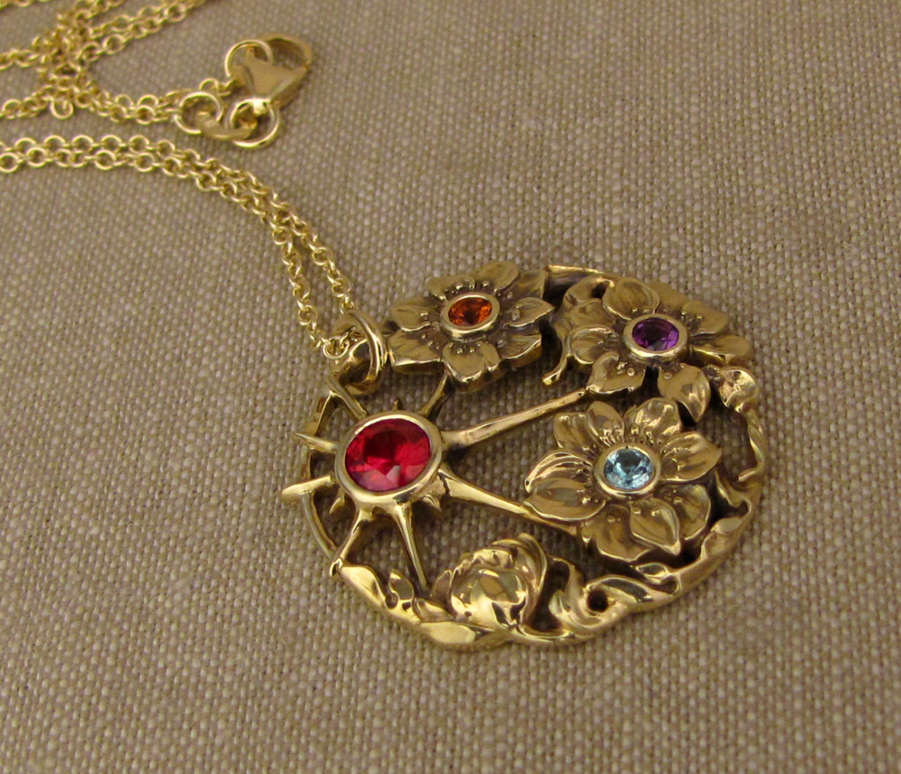 Custom-designed & hand-carved 'Mother's' pendant with ruby, blue zircon, citrine, and amethyst birthstones, in 18K yellow gold.