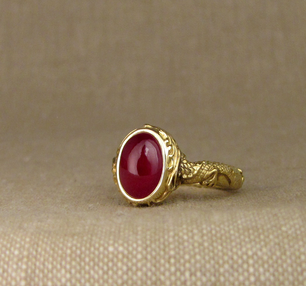 Hand carved ruby cabochon solitaire with Chinese dragon and phoenix chasing each other around the band. 18K yellow gold